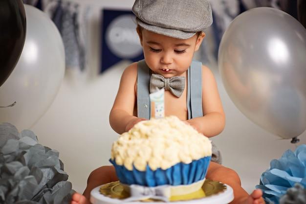 Schattige gelukkige babyjongen met een cake om een verjaardag te vieren