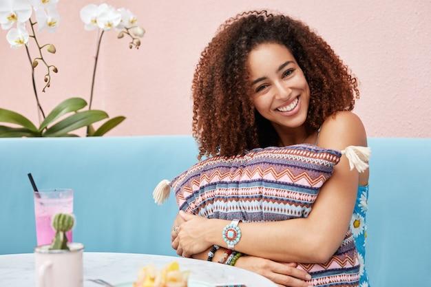 Schattige gelukkige donkere vrouw met afro kapsel, blij om compliment te ontvangen, omhelst kussen, drinkt smoothie in cafetaria