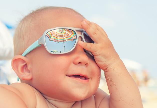 Schattige gelukkige grappige glimlachende schattige babyjongen op het strand