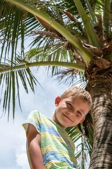 Schattige gelukkige jongen zittend op palmboom zee strand