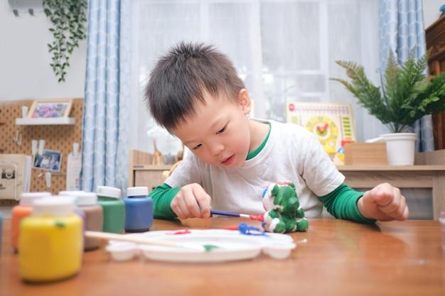 Schattige gelukkige kleine aziatische 3-4 jaar oude peuter jongen kind schilderij kleur op diy gips schilderij speelgoed, 3d gips standbeeld binnen thuis, creatief spel voor kinderen en peuters concept - selectieve aandacht