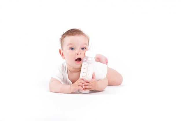 Schattige gelukkige kleine jongen in wit overhemd houdt melkfles