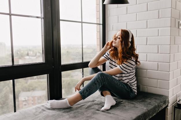 Schattige gember dame in spijkerbroek zittend op de vensterbank en muziek luisteren. blij krullend meisje poseren naast raam in koptelefoon.