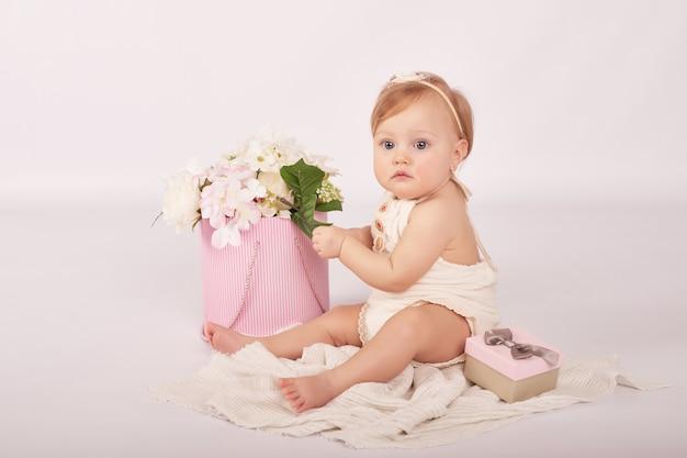 Schattige grappige baby met bloemen. schattige babymeisje.