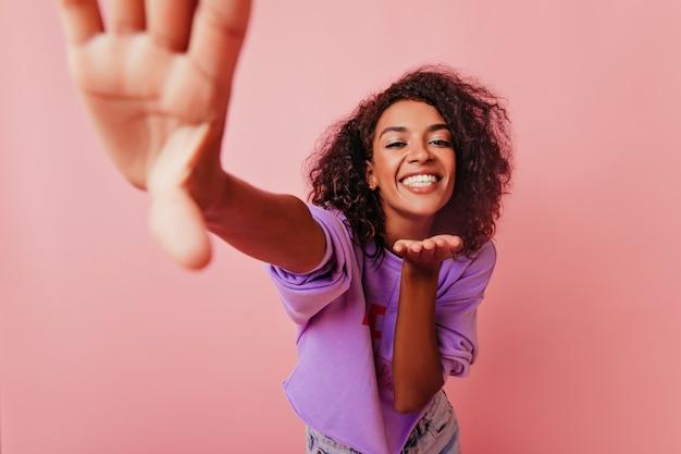 Schattige grappige vrouw die luchtkus verzendt. charmant afrikaans meisje dat selfie met geïnspireerde gezichtsuitdrukking maakt.