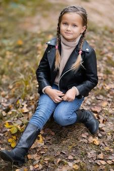 Schattige happy babymeisje in modieuze vrijetijdskleding in herfst natuurpark