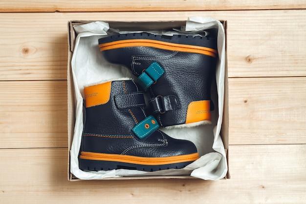 Schattige herfstlaarzen voor kinderen in een kartonnen doos op een houten vloer. bovenaanzicht