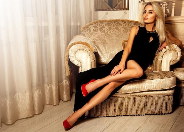 Schattige hete blonde vrouw in lange zwarte jurk en rode hoge hakken