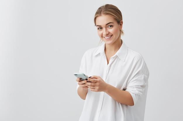 Schattige hipster blanke vrouw met blond haar controleert haar nieuwsfeed of berichten via sociale netwerken, met behulp van gratis wifi op mobiele telefoon, glimlachen, poseren
