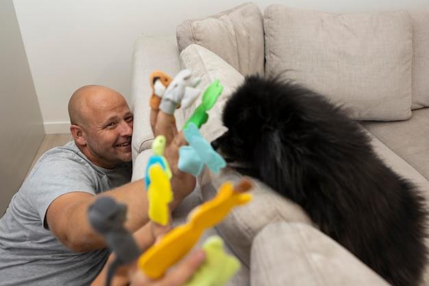 Schattige hond die naar zijn baasjes kijkt terwijl hij met poppen speelt