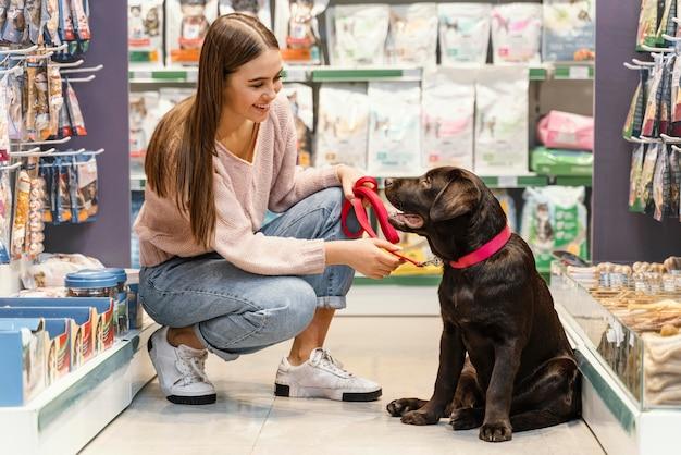 Schattige hond met vrouwelijke eigenaar bij de dierenwinkel