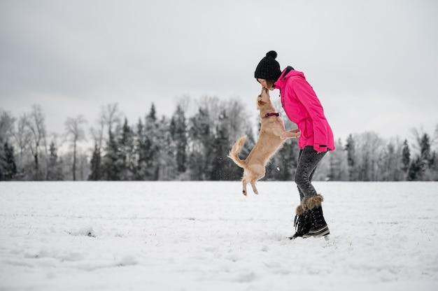 Schattige hond springen op om haar baasje een kus te geven terwijl ze buiten in de prachtige besneeuwde natuur is.