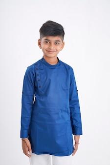 Schattige indiase kleine jongen in etnische slijtage en uitdrukking op wit tonen
