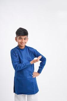 Schattige indiase kleine jongen in etnische slijtage en uitdrukking op witte achtergrond tonen