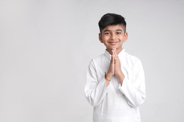 Schattige indiase kleine jongen in namaste of bidden stelt op witte achtergrond