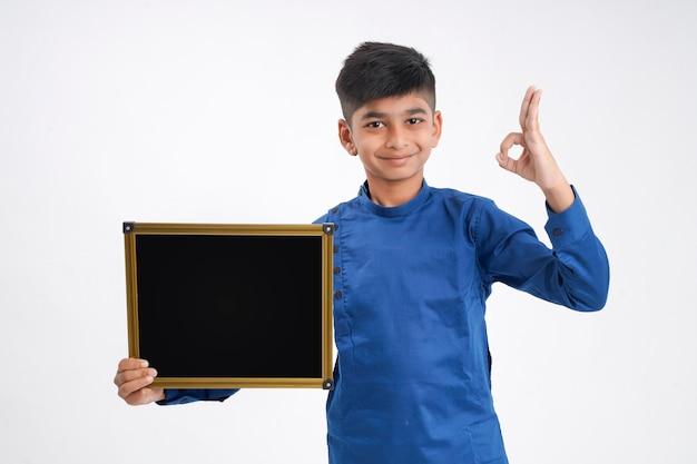 Schattige indiase kleine jongen zwarte bord met kopie ruimte tonen op witte achtergrond