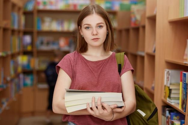 Schattige intelligente vrouwelijke jongere houdt boek vast, draagt rugzak, poseert in schoolbibliotheek, zoekt naar noodzakelijk materiaal, bereidt zich voor op examen of schrijft diplomapapier. mensen, jeugd, studeren concept