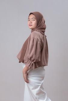 Schattige jonge aziatische moslimvrouw in hijab lichte kleding poseren geïsoleerd op grijze achtergrond studio portret