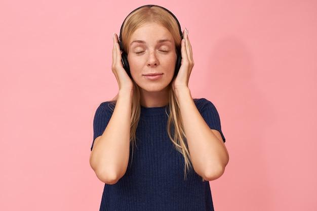 Schattige jonge blanke vrouw die met sproeten de ogen gesloten houdt en geniet van een nieuw album van haar favoriete muziekkunstenaar met een draadloze hoofdtelefoon
