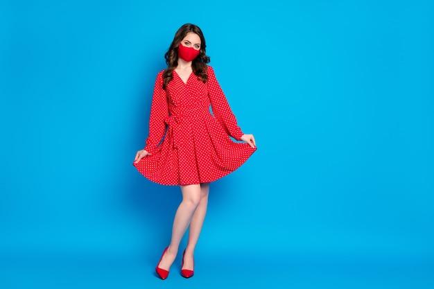 Schattige jonge brunette dame in rode mini-jurk draagt een medisch masker poseren