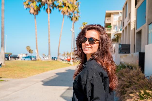 Schattige jonge brunette meisje in zonnebril loopt langs de waterkant van los angeles met palmbomen