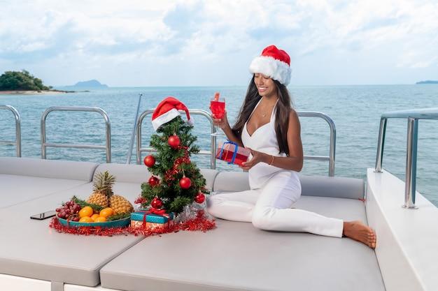 Schattige jonge brunette viert nieuwjaar en kerstmis op een jachtcruise.