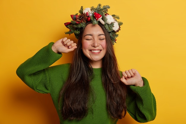 Schattige jonge dame glimlacht aangenaam met feestelijke krans op het hoofd
