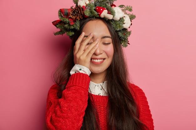Schattige jonge dame glimlacht aangenaam met feestelijke krans op het hoofd Gratis Foto