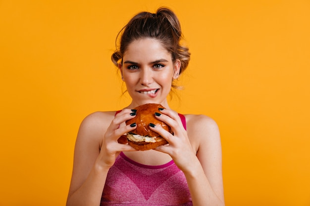 Schattige jonge dame hamburger eten