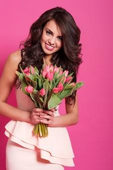 Schattige jonge dame met boeket roze tulpen