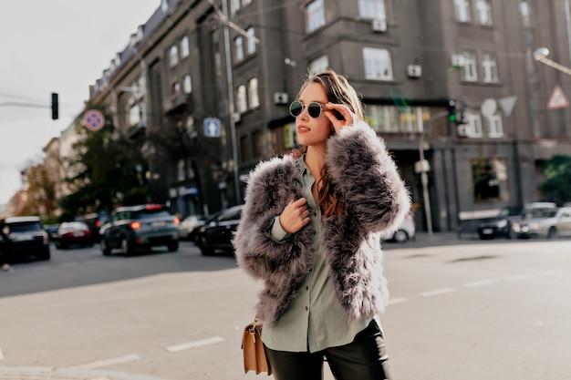 Schattige jonge dame met tas dragen bontjas en donkere zonnebril poseren op stad