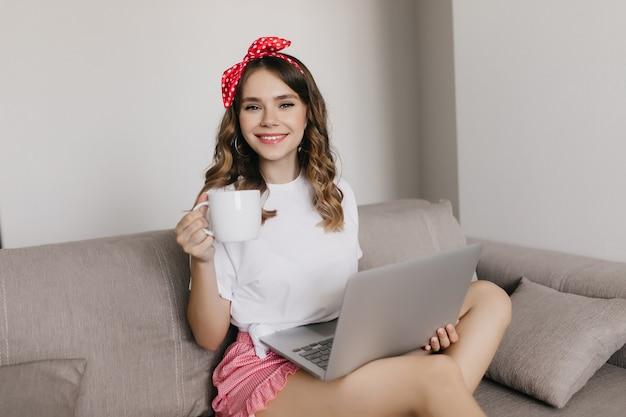 Schattige jonge dame thee drinken en surfen op internet. indoor portret van geïnteresseerd meisje chiling met laptop op de bank.