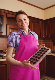 Schattige jonge europese vrouw chocolatier in roze schort staande in de huiskeuken en schattig glimlachen terwijl poseren op camera met mallen vol chocoladeschelpen