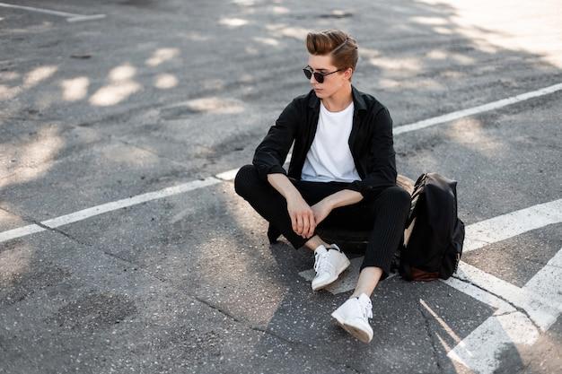 Schattige jonge hipster man in zwarte elegante stijlvolle kleding in trendy zonnebril