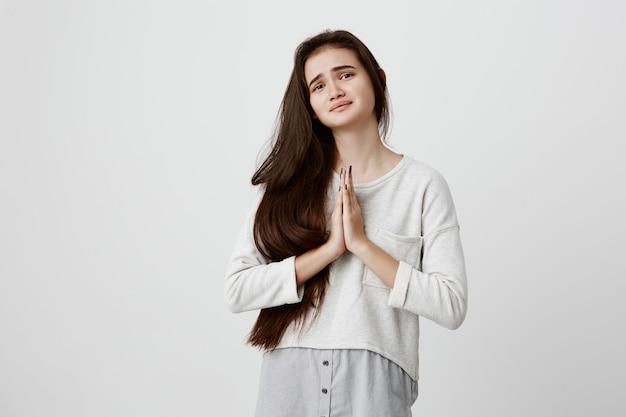 Schattige jonge hoopvolle donkerharige vrouw, gekleed in een casual top met lange mouwen die de handpalmen tegen elkaar drukt, zich ongerust en wanhopig voelt terwijl ze bidt voor het welzijn en de goede gezondheid van haar ouders.