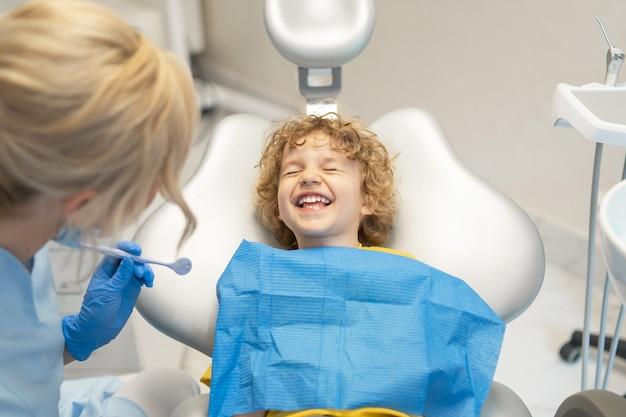 Schattige jonge jongen bezoekende tandarts en het hebben van zijn tanden gecontroleerd door vrouwelijke tandarts in tandartspraktijk