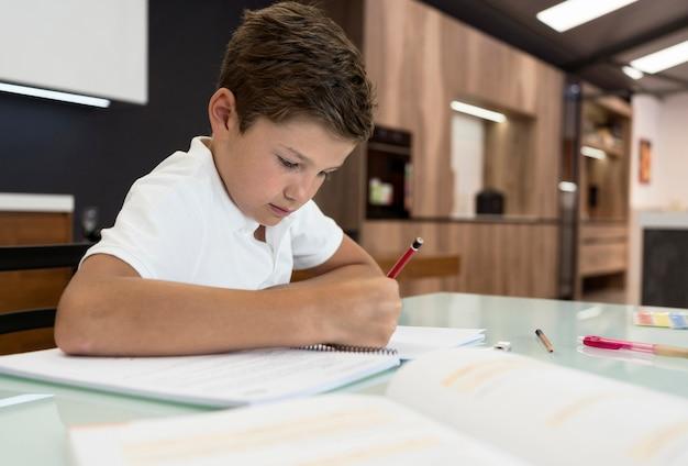 Schattige jonge jongen die zijn huiswerk doet