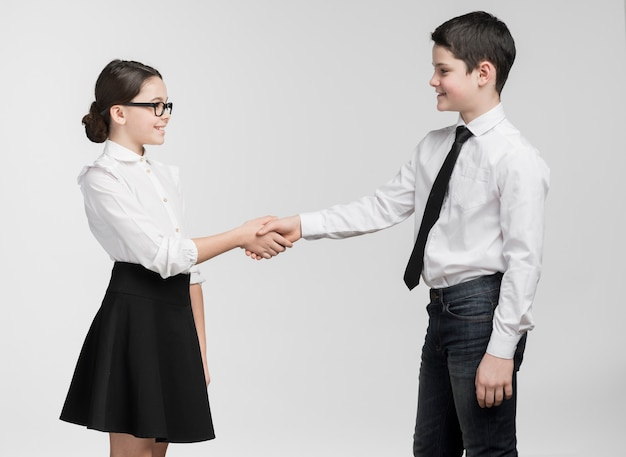 Schattige jonge jongen en meisje handen schudden