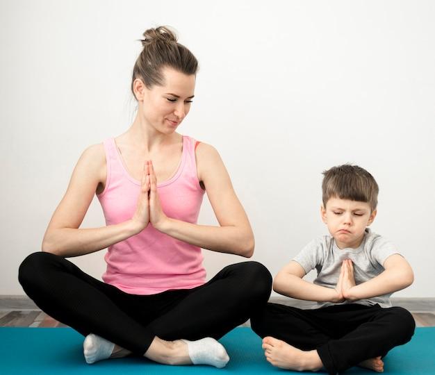 Schattige jonge jongen het beoefenen van yoga met moeder
