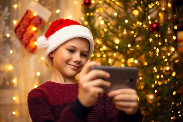 Schattige jonge jongen maakt een selfie in de hoed van de kerstman, versierde dennenboom. het concept van kerstmis.