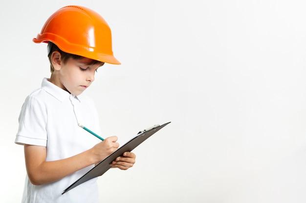 Schattige jonge jongen met helm schrijven
