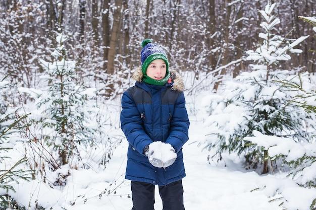 Schattige jonge jongen speelt met sneeuw, veel plezier, glimlacht. tiener in winterpark. actieve levensstijl, winter