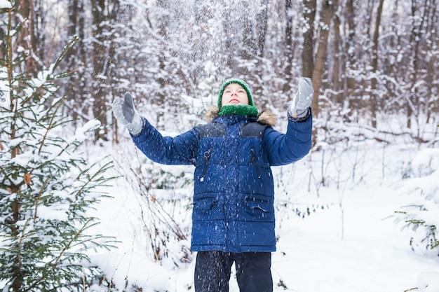 Schattige jonge jongen speelt met sneeuw, veel plezier, glimlacht. tiener in winterpark. actieve levensstijl, winteractiviteit, winterspelen in de buitenlucht, sneeuwballen.