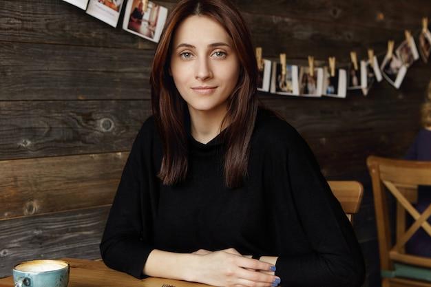 Schattige jonge kaukasische brunette vrouw met losse kapsel handen rusten op tafel terwijl u geniet van haar vrije dag, ontspannen in café tijdens koffiepauze, wachten op vriend, op zoek met glimlach