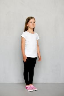 Schattige jonge kind met lang haar in wit t-shirt en zwarte joggingbroek poseren