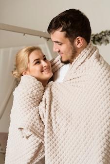 Schattige jonge man en vrouw bedekt met een deken