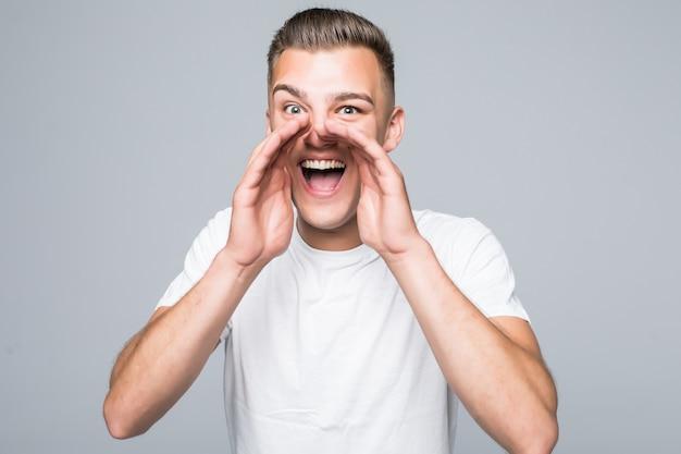 Schattige jonge man jongen schreeuwt terwijl geïsoleerd op een witte muur