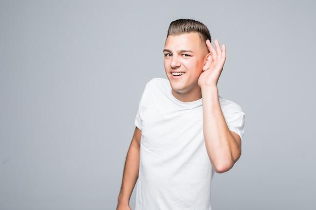 Schattige jonge man jongen shows hoor je niet ondertekenen geïsoleerd op een witte muur