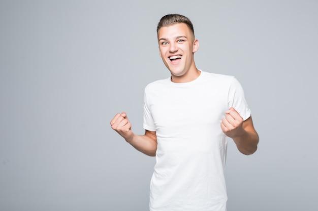 Schattige jonge man jongen toont gelukkig overwinningsteken geïsoleerd op een witte muur