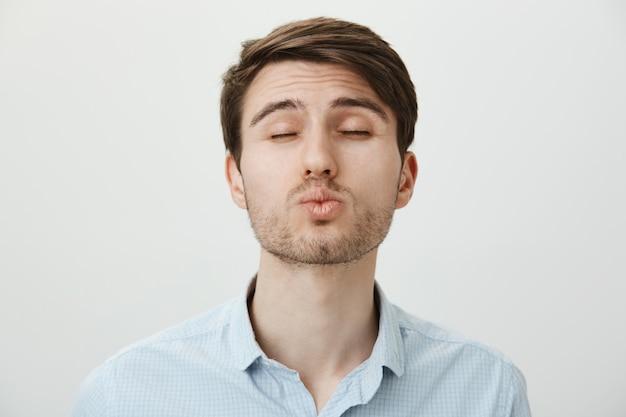 Schattige jonge man met borstelige ogen dicht als wachten op een kus